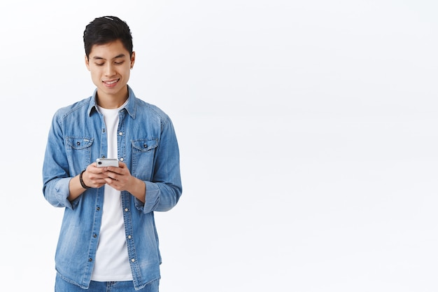 Hübscher junger asiatischer männlicher student, der eine sms mit freund schreibt, smartphone hält, mit handy, internet in verbindung bleibt, soziales netzwerk online scrollen, weiße wand