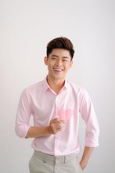 Hübscher junger asiatischer mann, der herzförmigen valentinstag aus papier hält