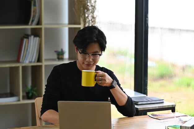 Hübscher junger asiatischer mann, der kaffee trinkt und mit laptop-computer arbeitet.