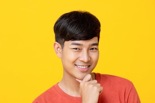 Hübscher junger asiatischer mann, der mit der hand auf kinn lächelt