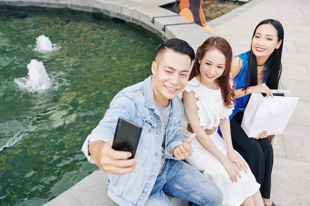Hübscher junger asiatischer mann, der mit seinen freundinnen am brunnen sitzt und selfie nimmt, nachdem er zusammen im einkaufszentrum einkauft