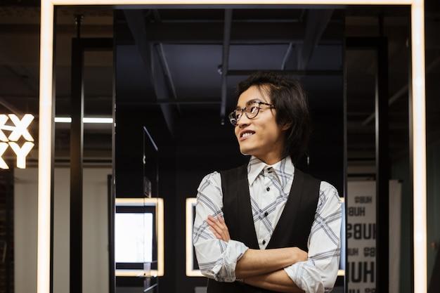 Hübscher junger asiatischer mann, der mit verschränkten armen steht