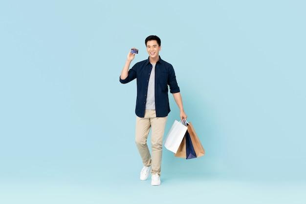 Hübscher junger asiatischer mann, der taschen trägt, die mit kreditkarte lokalisiert auf hellblauer wand tragen