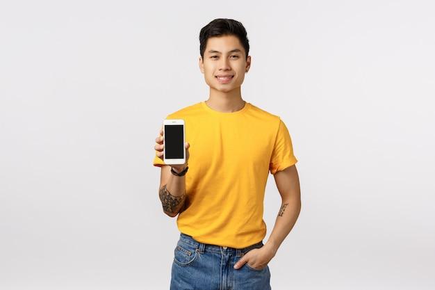 Hübscher junger asiatischer mann im gelben t-shirt, das smartphone hält