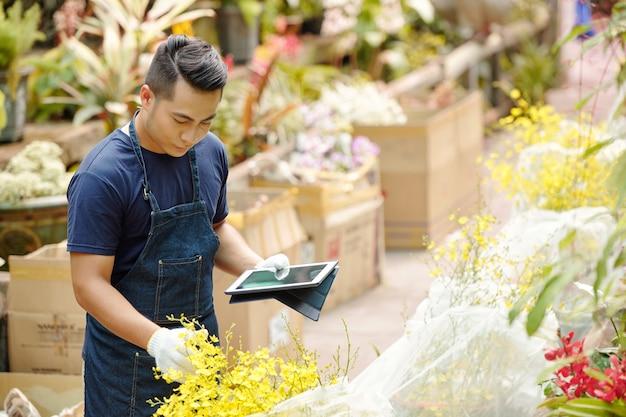 Hübscher junger asiatischer mann mit handschuhen bei der arbeit mit pflanzen im gewächshaus