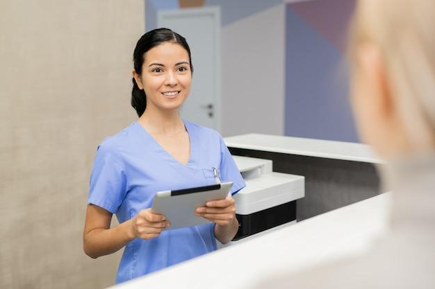 Hübscher junger assistent mit digitalem tablett, der an der rezeption steht, während neuer patient in kliniken registriert wird