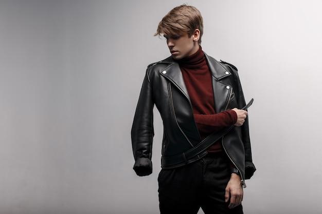 Hübscher junger attraktiver mann mit einer frisur in einer trendigen schwarzen lederjacke in burgunderfarbenem stilvollem golf und stilvollen schwarzen jeans steht und posiert in einem raum nahe einer weißen wand. moderner typ mit stil