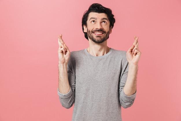 Hübscher junger bärtiger brünetter mann, der pullover trägt, der über rosa steht und daumen drückt für glück