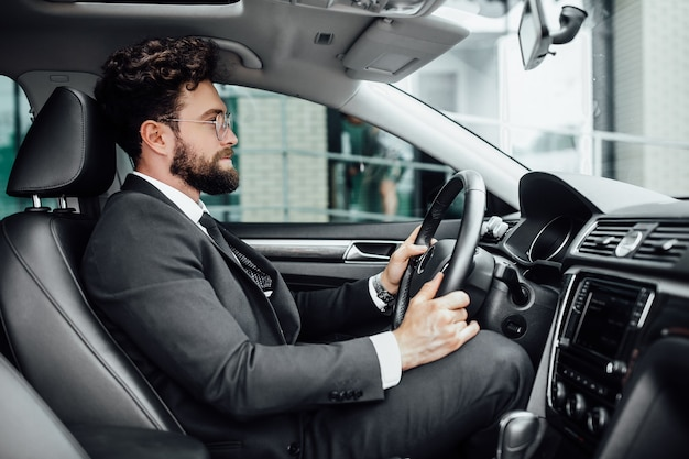 Hübscher junger bärtiger fahrer im vollen anzug, der ein auto fährt