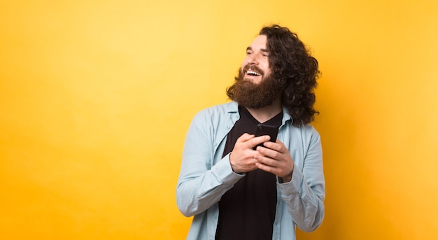 Hübscher junger bärtiger hipster-mann, der smartphone benutzt und über gelbem hintergrund lächelt