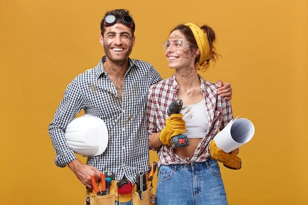 Hübscher junger bärtiger ingenieur, der helm unter seinem arm hält und seine schöne kollegin in schutzbrille umarmt