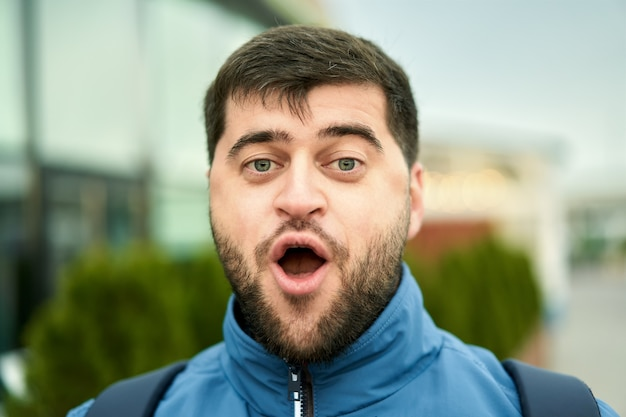 Hübscher junger bärtiger kaukasischer hipster mit kurzen braunen haaren und offenem mund geht im freien.