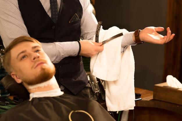 Hübscher junger bärtiger mann am friseursalon