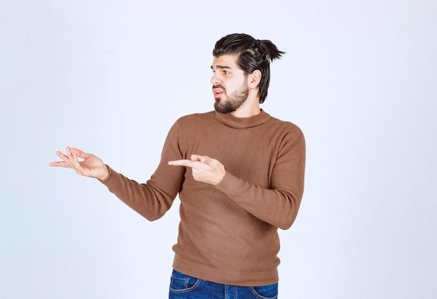 Hübscher junger bärtiger mann, der auf grauweißem hintergrund weg zeigt. foto in hoher qualität