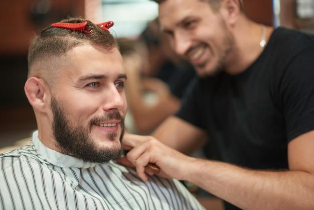 Hübscher junger bärtiger mann, der lächelnd wegschaut, während professioneller friseur ihm einen haarschnitt kopyspace gibt.