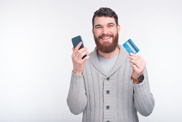 Hübscher junger bärtiger mann hält eine kreditkarte und ein smartphone auf einem weißen hintergrund.