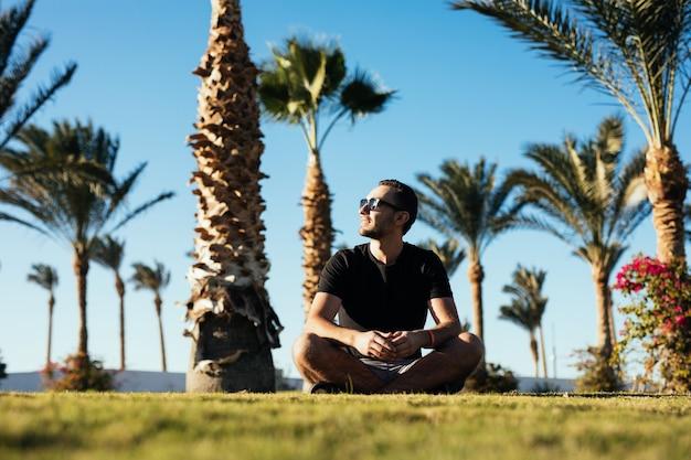 Hübscher junger bärtiger mann in der sonnenbrille, die auf dem gras unter palmen im luxusferienort der sommerferien sitzt