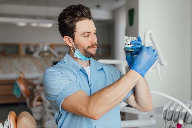 Hübscher junger bärtiger zahnarzt im weißen kittel hält plastiklajot und zahnbürste, während er in seinem büro steht.