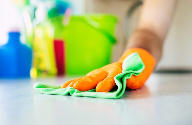 Hübscher junger bartmann in einem t-shirt wischt den tisch mit spezialwerkzeugen in der küche ab, während das haus putzt