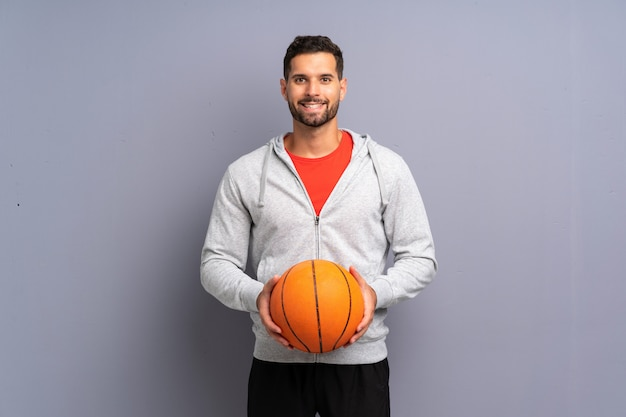 Hübscher junger basketball-spielermann, der viel lächelt