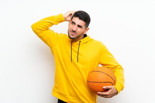 Hübscher junger basketball-spielermann über der lokalisierten weißen wand, die zweifel und mit hat, verwirren gesichtsausdruck