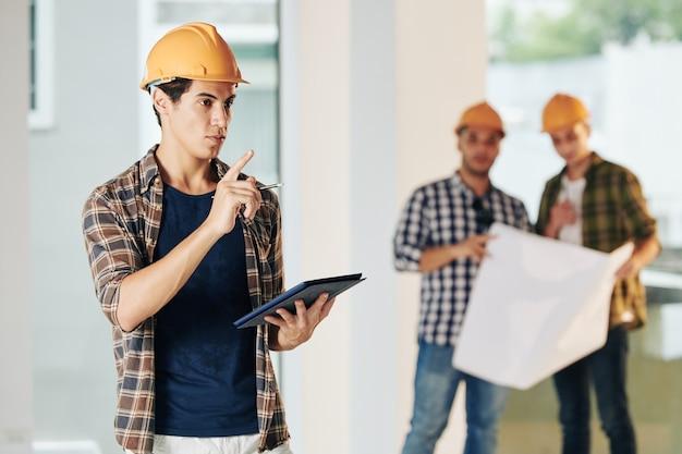 Hübscher junger bauingenieur im helm und im karierten hemd, die baustelle inspizieren und notizen im dokument auf tablet-computer machen