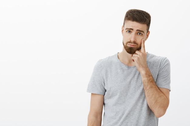 Hübscher junger berührter kerl mit bart, der traurigen und düsteren ausdruck macht, der auf augenlid zeigt, als ob sie eine träne zeigt, die bedauern oder traurigkeit ausdrückt, die unzufrieden steht und über graue wand weint
