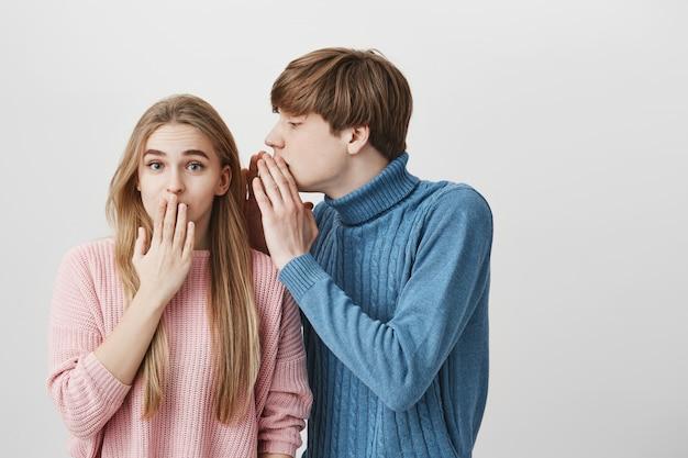 Hübscher junger blonder männlicher student im blauen pullover, der etwas in das ohr des stilvollen blonden mädchens flüstert