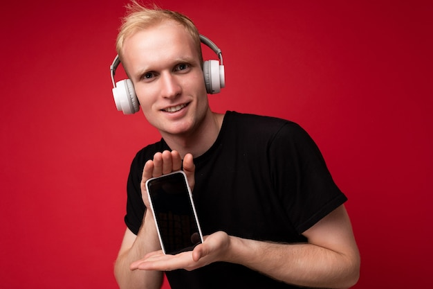Hübscher junger blonder mann, der ein lässiges schwarzes t-shirt und kopfhörer trägt und podcasts hört, die smartphone mit leerem bildschirm für modell mit blick auf die kamera halten