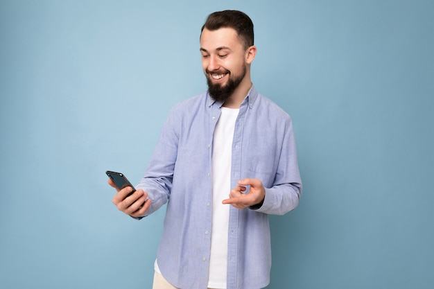 Hübscher junger, brünetter, unrasierter mann mit bart, der ein stilvolles weißes t-shirt und ein blaues hemd trägt, isoliert auf blauem hintergrund mit leerem raum, der in der hand hält und das telefon mit blick auf das display verwendet.