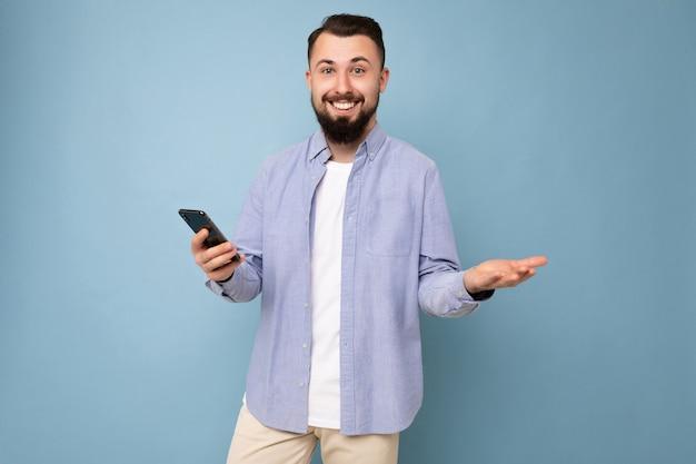 Hübscher junger brünetter unrasierter mann mit bart, der ein stilvolles weißes t-shirt und ein blaues hemd trägt, isoliert