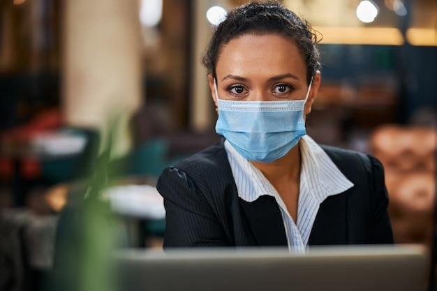 Hübscher junger büroangestellter mit maske beim sitzen im café sitting