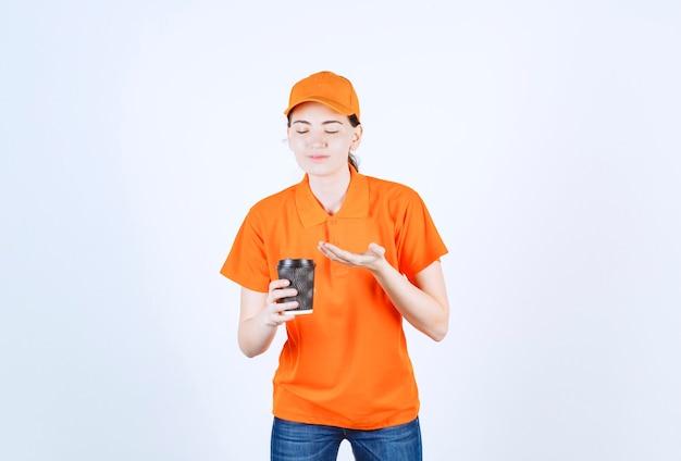 Hübscher junger coureir, der ihren kaffee mit grauer grundfarbe zart zeigt