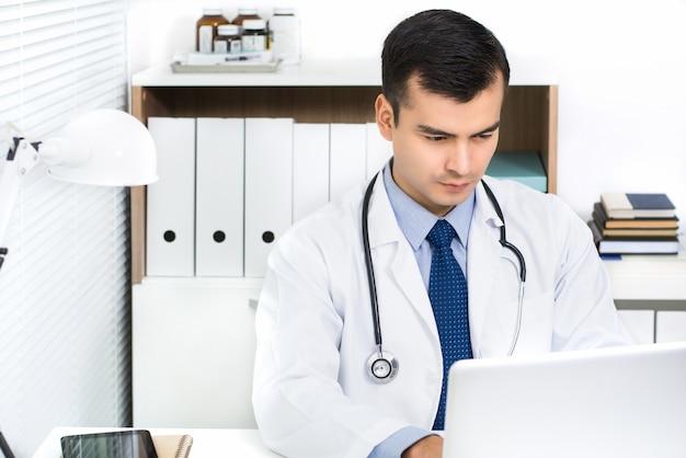 Hübscher junger doktor, der an der laptop-computer online sucht nach informationen arbeitet