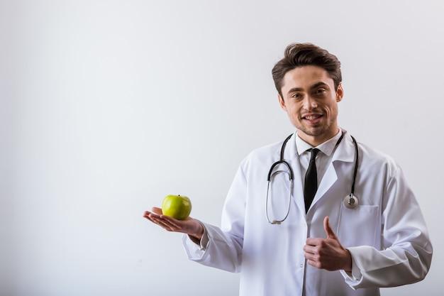 Hübscher junger doktor im weißen kleid und mit stethoskop. diät-konzept