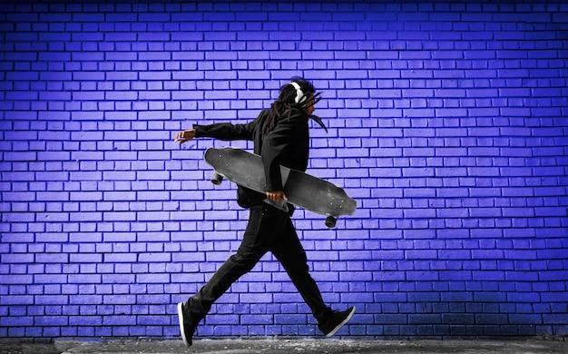 Hübscher junger dreadlocks-skater mit kopfhörern, die in einem anzug nahe der blauen wand auf der straße laufen.