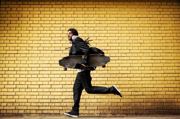 Hübscher junger dreadlocks-skater mit kopfhörern, die in einem su laufen