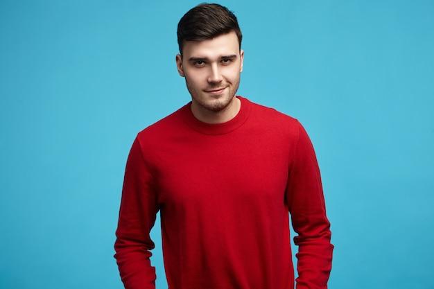 Hübscher junger dunkelhaariger mann, der stilvollen roten pullover mit langen ärmeln trägt, die an kamera lächeln
