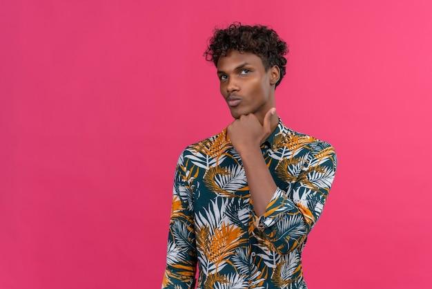 Hübscher junger dunkler hautmann, der gelegenheiten abwägt, die in nachdenklicher haltung mit faust auf kinn stehen, das augenbrauen anhebt, die obere rechte ecke betrachten