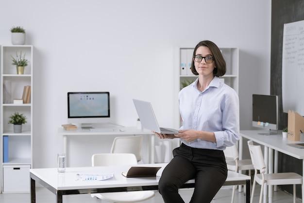 Hübscher junger eleganter angestellter mit laptop, der auf schreibtisch sitzt, während über geschäftsprojekt im büro arbeitet