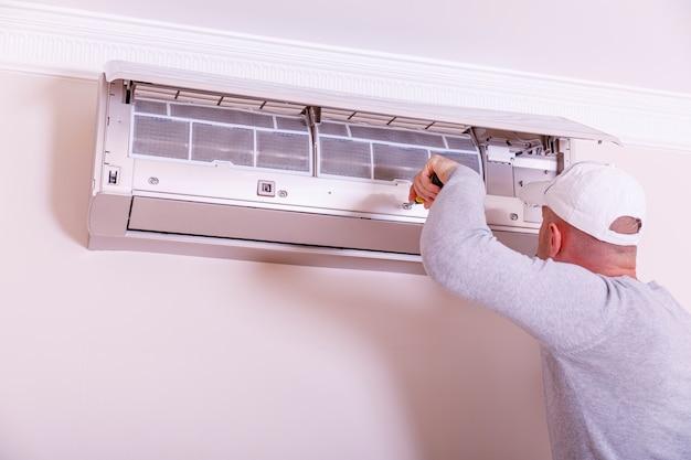 Hübscher junger elektriker, der klimaanlage in einem kundenhaus installiert. reinigung der klimaanlage. mann in handschuhen überprüft den filter.