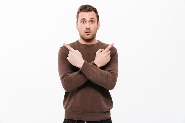 Hübscher junger entsetzter mann, der copyspace zeigt.