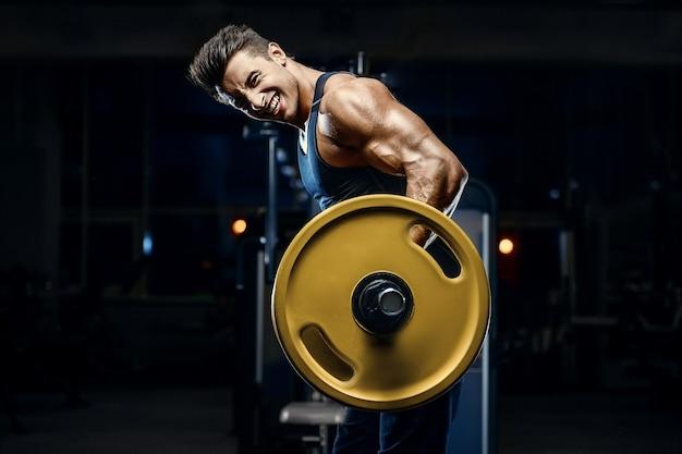 Hübscher junger fit muskulöser kaukasischer mann des modellauftrittstrainingstrainings im fitnessstudio, das gewicht zunimmt, das muskeln aufpumpt und fitness- und bodybuilding-sportkonzept aufwirft