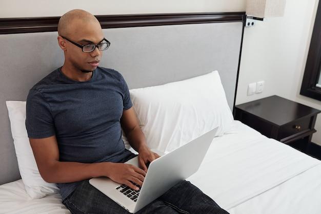 Hübscher junger fit schwarzer mann in gläsern, die auf bett im hotelzimmer oder im schlafzimmer sitzen und am laptop arbeiten