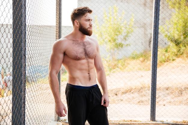 Hübscher junger fitness-mann mit nacktem oberkörper, der sich während des trainings im freien ausruht