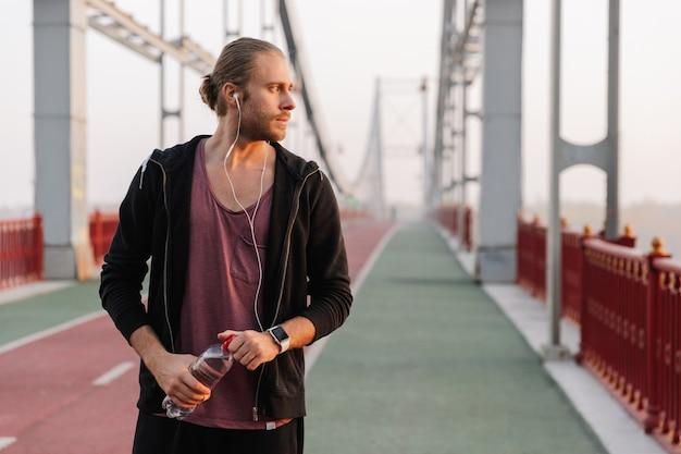 Hübscher junger fitter sportler, der musik mit drahtlosen kopfhörern auf einer brücke hört und wasserflasche hält