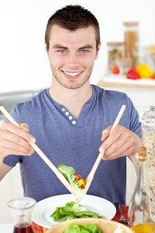 Hübscher junger fleisch fressender ein salat, der an der kamera lächelt