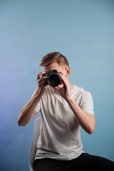 Hübscher junger fotograf, der kamera auf blauem hintergrund verwendet. mann, der eine professionelle kamera verwendet. porträt des kerls, der fotokamera betrachtet