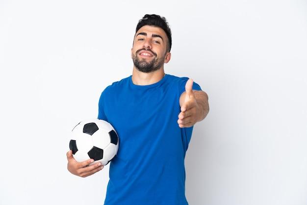 Hübscher junger fußballspieler mann über isolierter wand händeschütteln für das schließen eines guten geschäfts