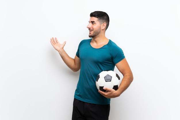 Hübscher junger fußballspielermann auf weißer wand mit überraschungsgesichtsausdruck